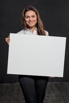 Smiley feminino segurando a folha de papel em branco