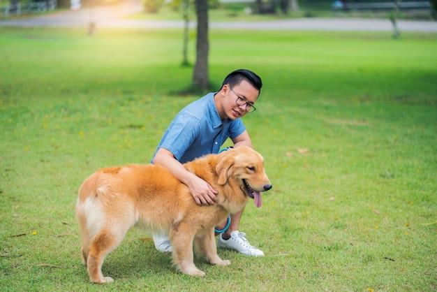 Smiley homem de camisa azul jogar com cão lindo golden retriever no jardim