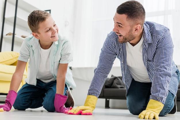 Smiley homem e menino limpando o chão