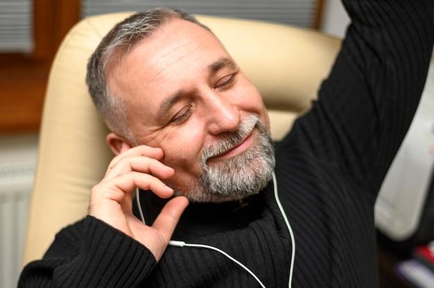 Smiley homem maduro ouvindo música embora fones