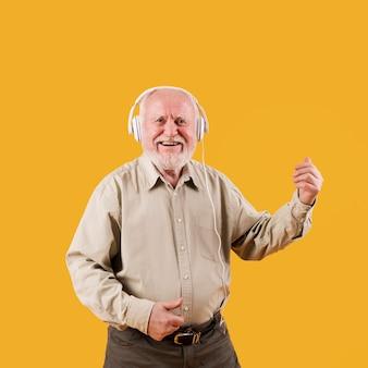 Smiley homem mais velho tocando quitar imaginário