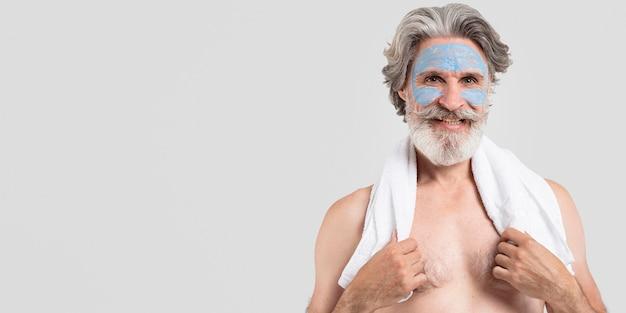 Smiley homem sênior com máscara facial e toalha