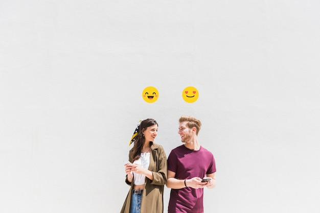 Smiley icon over smiling jovem casal usando smartphone
