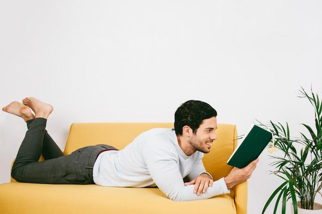 Smiley jovem lendo um livro no sofá