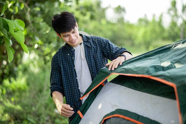Smiley jovem viajante montando uma barraca em um acampamento na floresta nas férias de verão