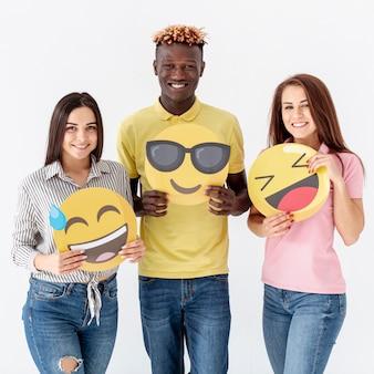 Smiley jovens amigos segurando emoji