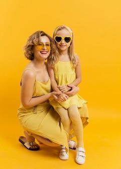 Smiley mãe e filha com óculos de sol