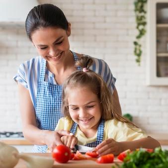Smiley mãe e filha cozinhar