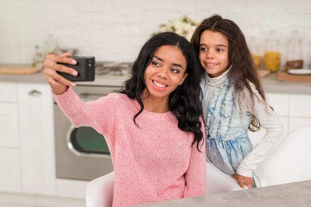 Smiley mãe e filha tirando fotos