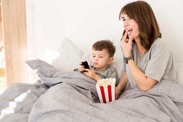 Smiley mãe e filho comendo pipoca