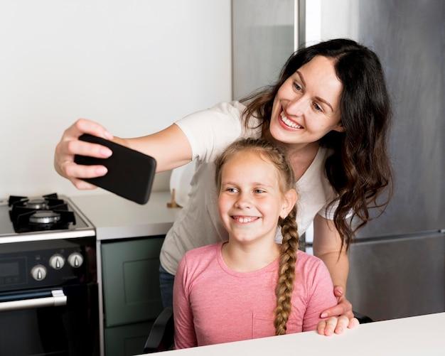 Smiley mãe e menina tomando selfie