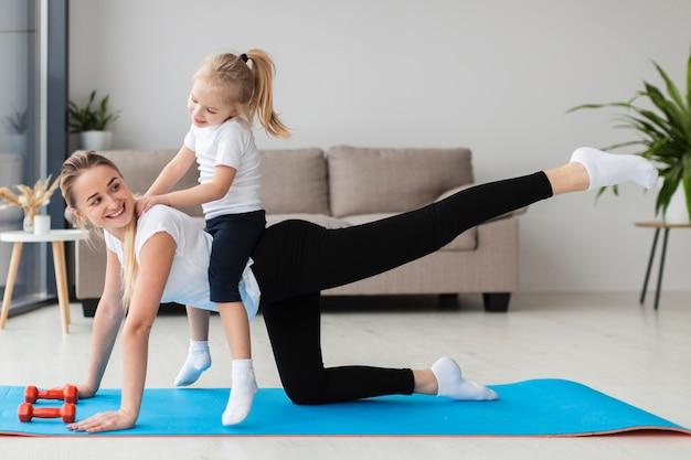 Smiley mãe exercitando em casa com a filha