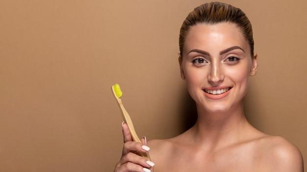 Smiley mulher adulta segurando a escova de dentes