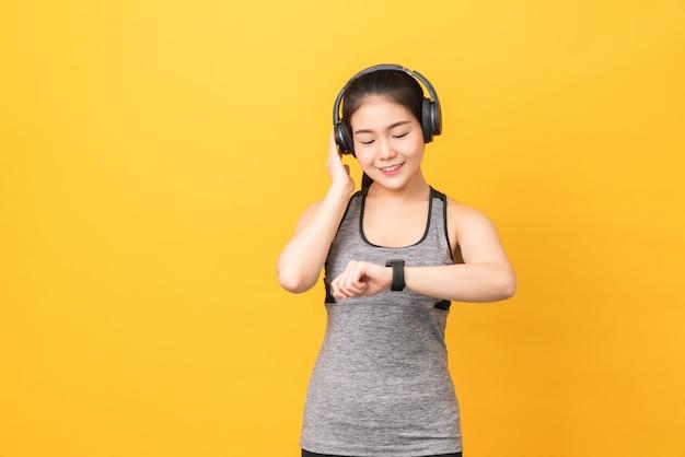 Smiley mulher asiática vestindo roupas esportivas olhando smartwatch e fones de ouvido na parede laranja