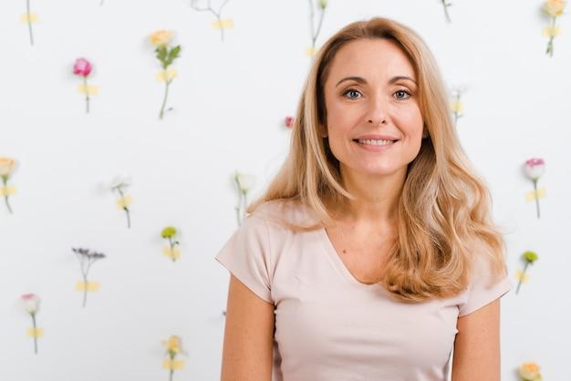 Smiley mulher bonita com parede floral