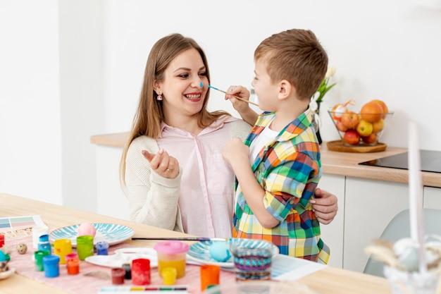 Smiley mulher e filho pintando ovos