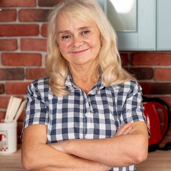 Smiley mulher idosa em pé na cozinha