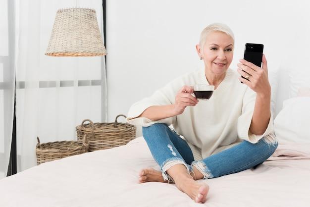 Smiley mulher idosa segurando a xícara de café e olhando para o telefone na cama