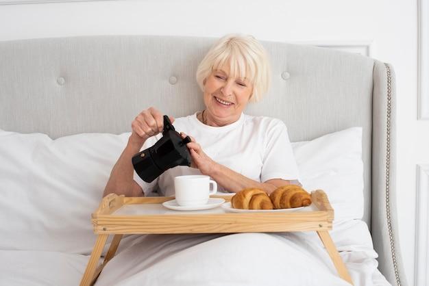 Smiley mulher idosa segurando chaleira no quarto
