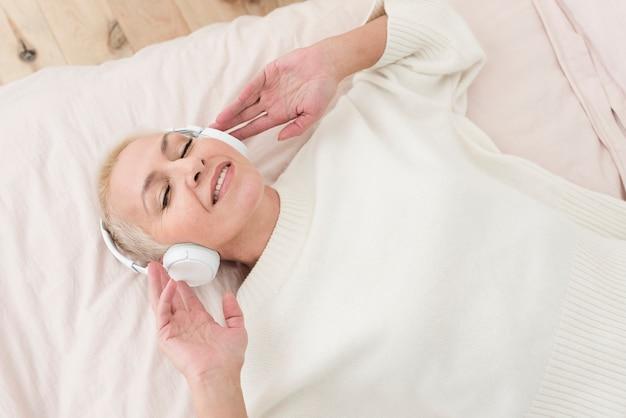 Smiley mulher madura curtindo música em fones de ouvido na cama