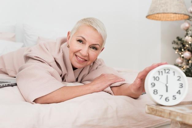 Smiley mulher madura em roupão posando na cama com relógio