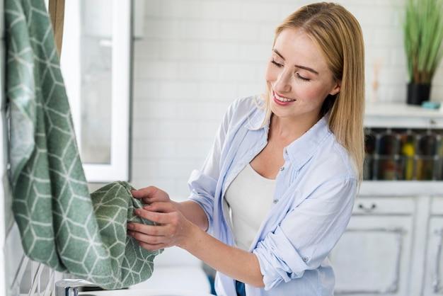 Smiley mulher secando as mãos com a toalha após a lavagem