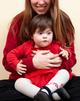 Smiley mulher segurando criança com síndrome de down