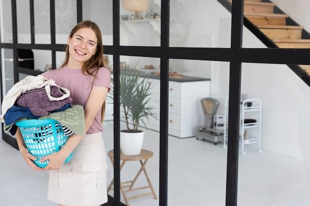 Smiley mulher segurando uma cesta de roupas