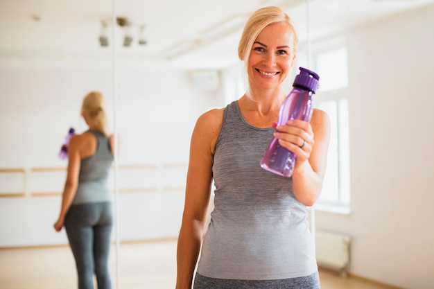 Smiley mulher sênior segurando uma garrafa de água