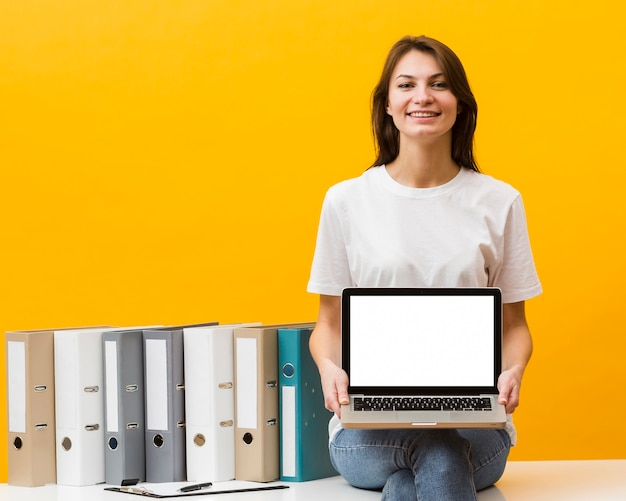 Smiley mulher sentada na mesa e segurando laptop