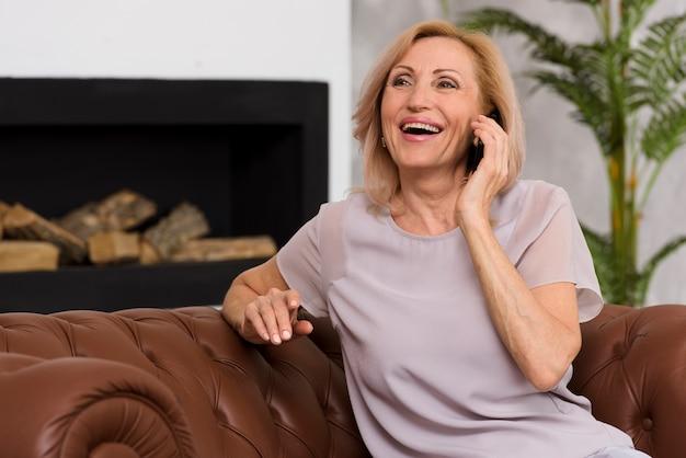 Smiley mulher sentada no sofá enquanto fala ao telefone