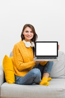 Smiley mulher sentada no sofá, mostrando seu laptop
