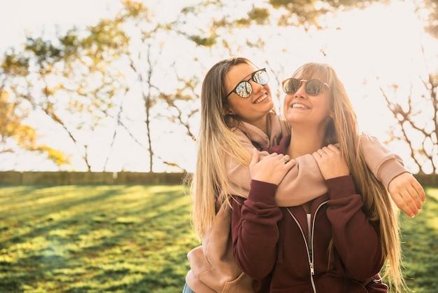 Smiley mulheres na luz solar abraçando