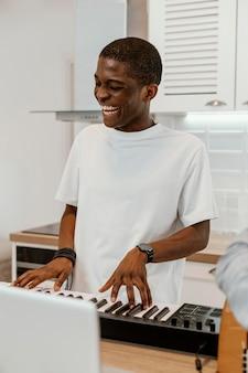 Smiley músico masculino em casa tocando teclado elétrico