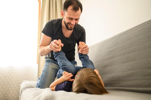 Smiley pai brincando com o filho no sofá