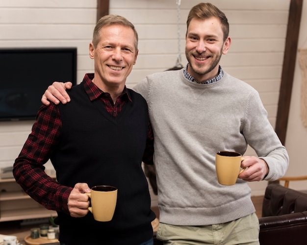 Smiley pai e filho posando enquanto segura copos