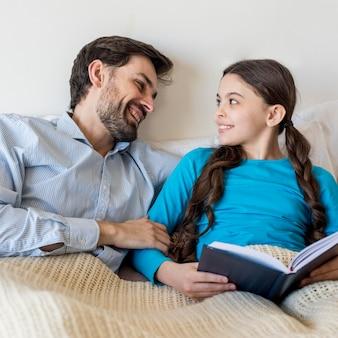 Smiley pai e menina na cama lendo