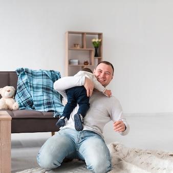 Smiley pai segurando o bebê em casa