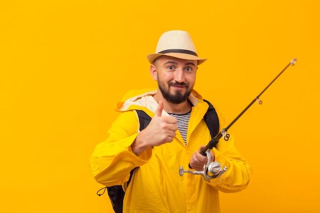 Smiley pescador desistindo polegares enquanto segura a vara de pescar