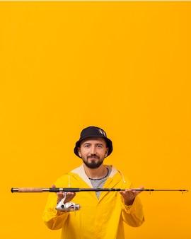 Smiley pescador segurando a vara de pescar com espaço de cópia