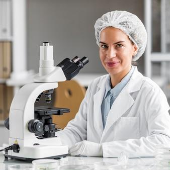 Smiley pesquisadora no laboratório de biotecnologia com microscópio