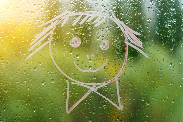 Smiley positivo em uma janela chuvosa de outono