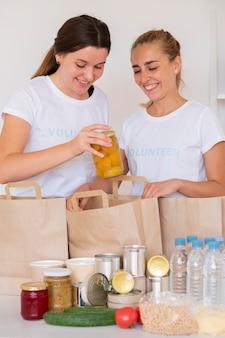Smiley se voluntaria com sacos de comida e água para doação