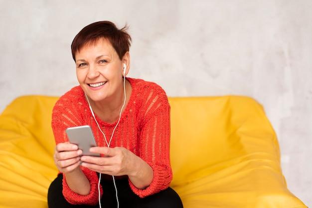 Smiley sênior feminino ouvindo música
