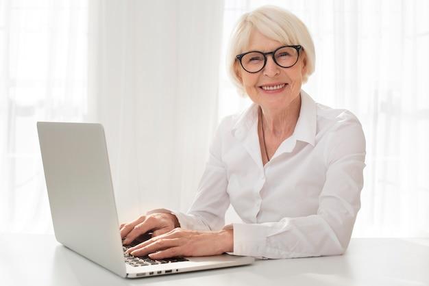 Smiley sênior trabalhando em um laptop
