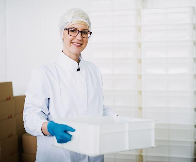 Smiley trabalhadora em roupas estéreis está guardando uma caixa de plástico.
