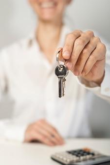 Smiley turva mulher segurando as chaves da casa