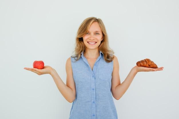Smiling beautiful woman holding apple e croissant