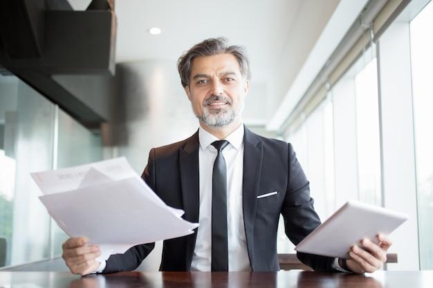 Smiling business man holding tablet e documentos