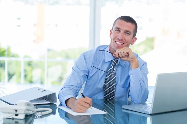 Smiling businessman escrevendo notas